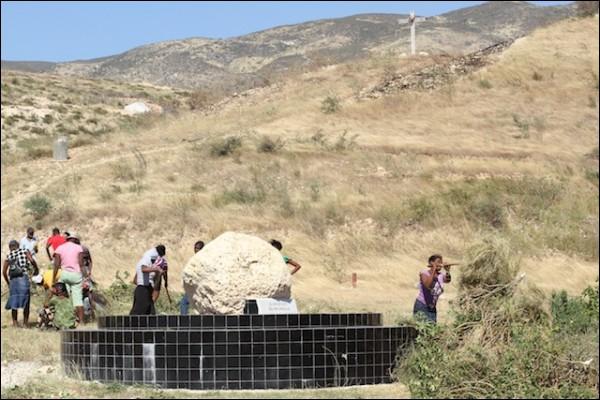 Des journaliers du CNE coupent des herbes sauvages autour de la grosse pierre où le monument à la mémoire des disparus du séisme du 12 janvier devait être érigéJean Marc Hervé Abélard
